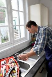 Carlsbad plumber fixes a kitchen sink with a crescent wrench and toolbox
